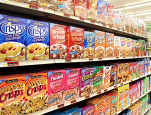 Photo of various boxes of cereal on store shelves.